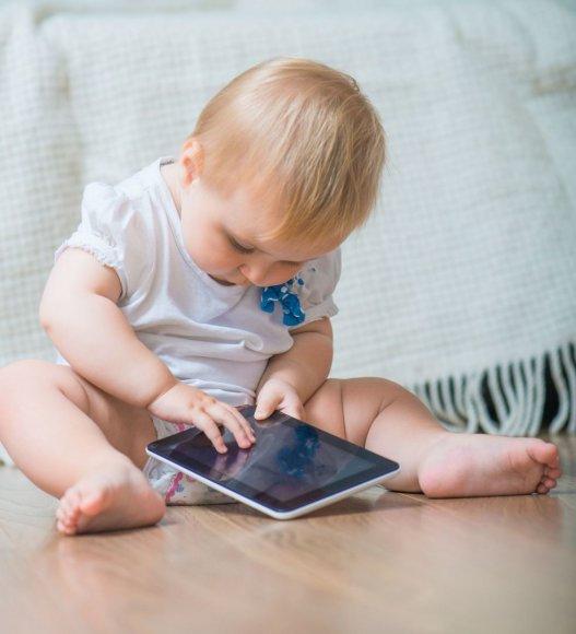 Vaikas su planšetiniu kompiuteriu