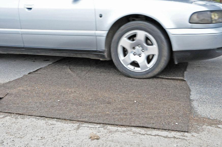 Automobilis važiuoja per dezinfekcinį kilimėlį