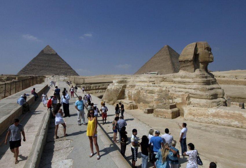 Turistai fotografuojasi prie Sfinkso ir Gizos piramidžių.