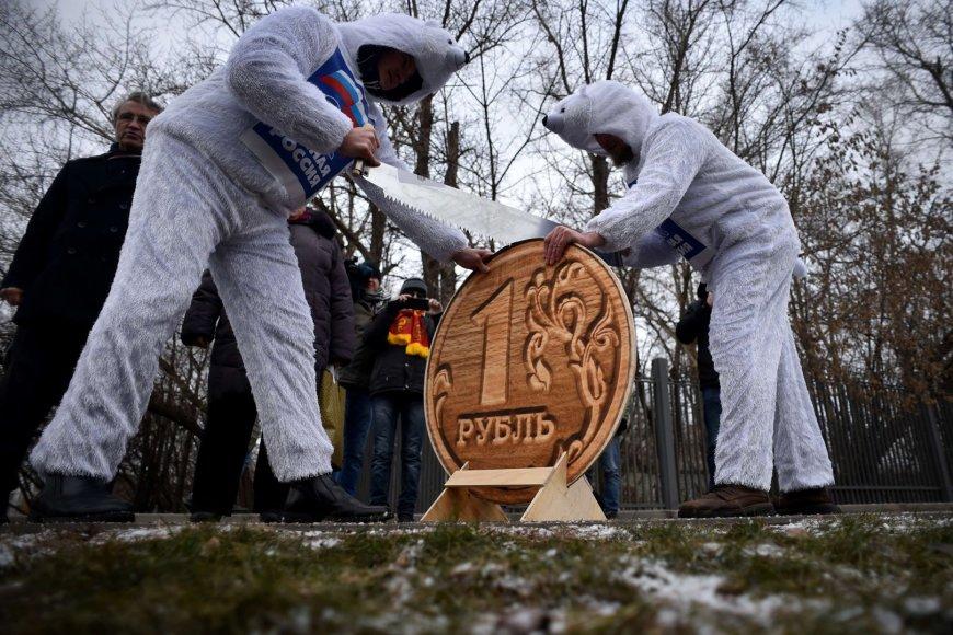 Baltaisiais lokiais apsirengę vyrai pjauna per pusę medinę rublio monetą