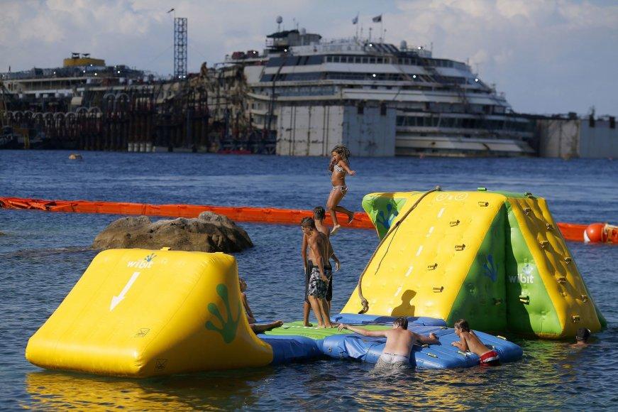"""Vaikai žaidžia netoli nuskendusio kruizinio laivo """"Costa Concordia"""""""