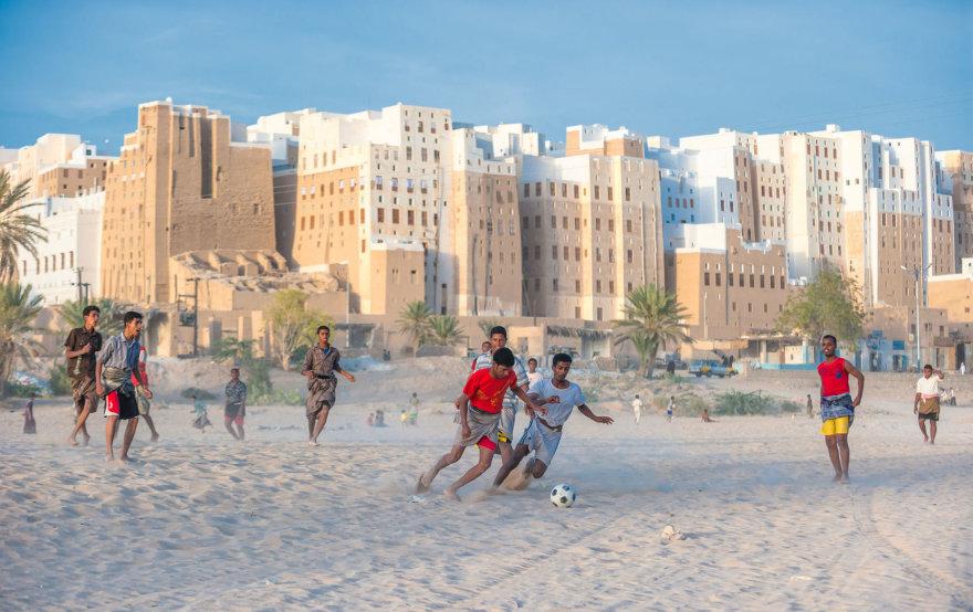 Vaikai priešais miestą žaidžia futbolą