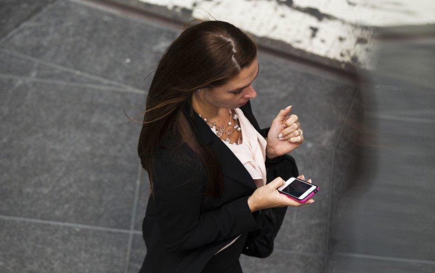 Moteris su išmaniuoju telefonu
