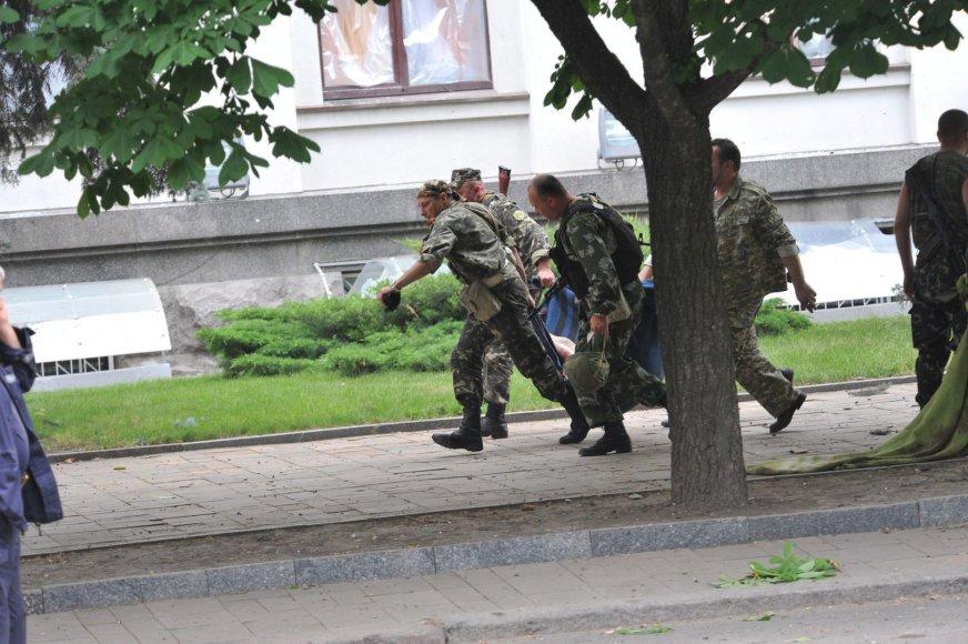 Luhanske prorusiški teroristai neša žuvusio kolegos kūną.
