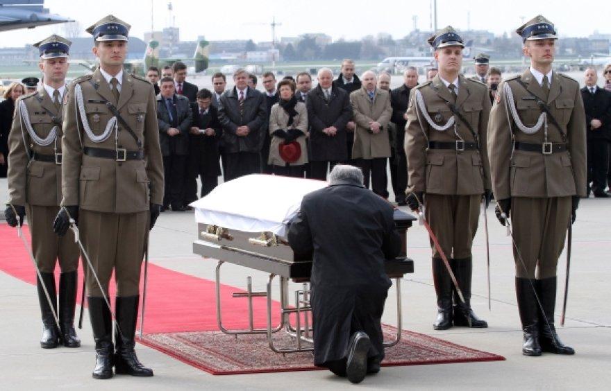 Jaroslawas Kaczynskis suklupęs prie savo brolio karsto