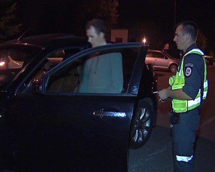 Ernestas Aleksonis ir policininkas prie notaro automobilio
