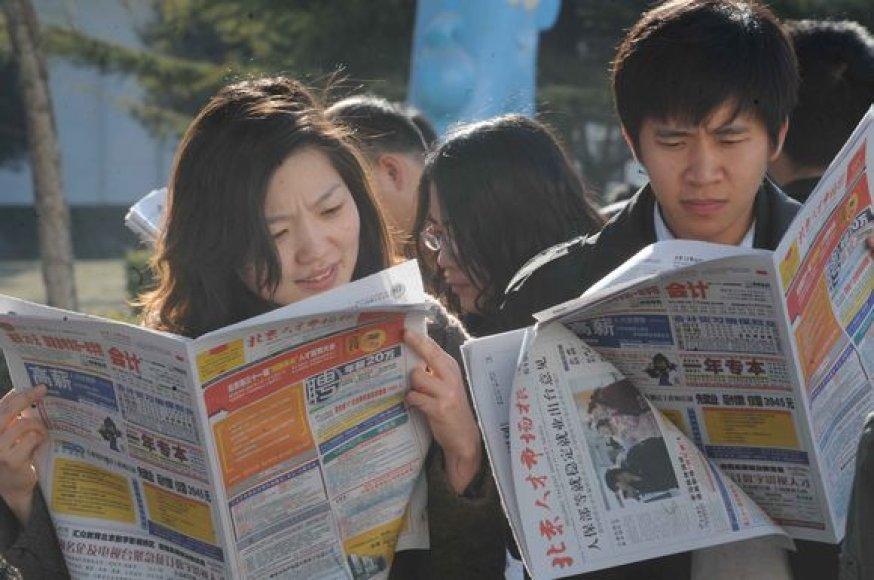 Darbo ieškantys kinai skaito skelbimus.