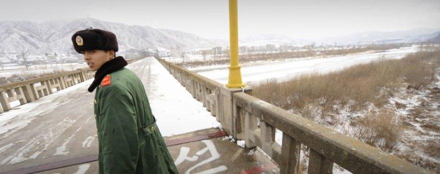 Šiaurės Korėjos pasienietis ant tilto per Tumeno upę, ant kurios ledo buvo sulaikytos amerikiečių žurnalistės.
