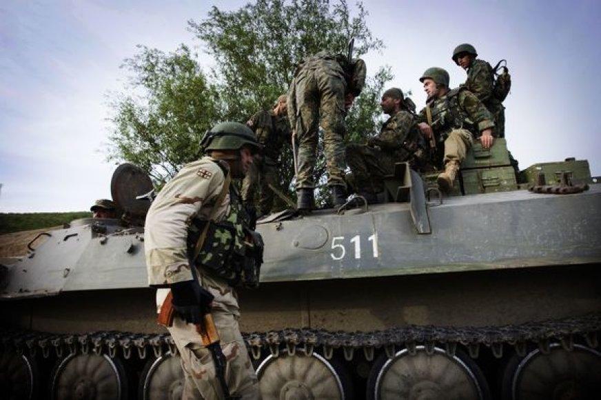 Gruzijos kariai sėda į šarvuotį.