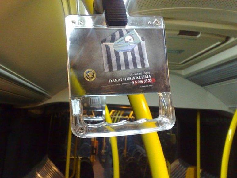 """Vilniaus autobusų keleiviai laikysis už rankenų, ant kurių matys visą parą veikiantį STT """"karštosios linijos"""" telefono numerį."""
