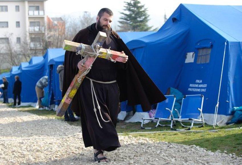 Nešinas kryžiumi vienuolis šv. Velykas minės drauge su nuo žemės drebėjimo nukentėjusiais italais, gyvenančiais šiame palapinių miestelyje.