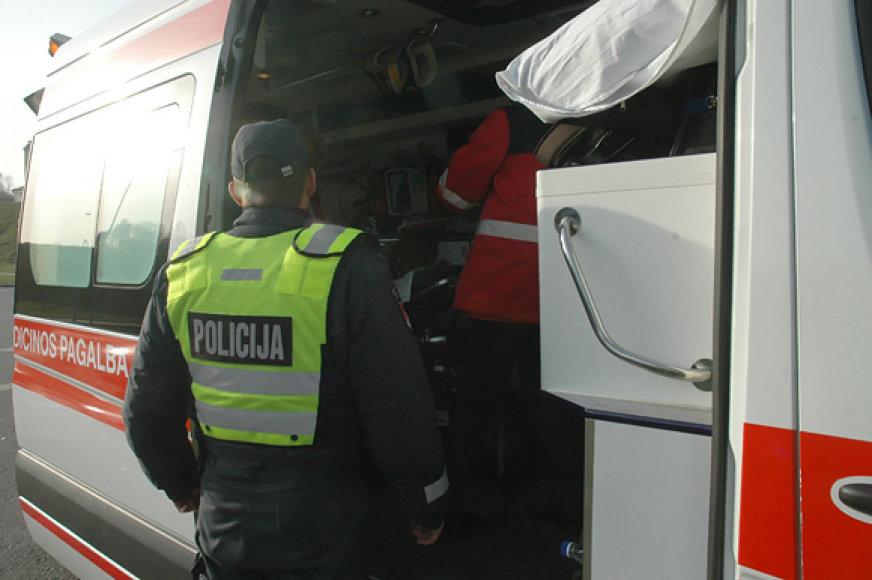 Policininkas prie greitosios pagalbos automobilio