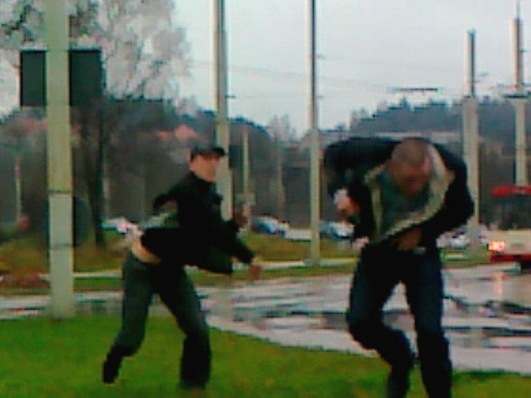 Muštynių akimirka: vyrukas su kepure meta į varžovą akmenį.
