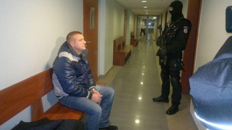 """Įtariamasis ir jį saugantis """"Aro"""" pareigūnas teisme"""