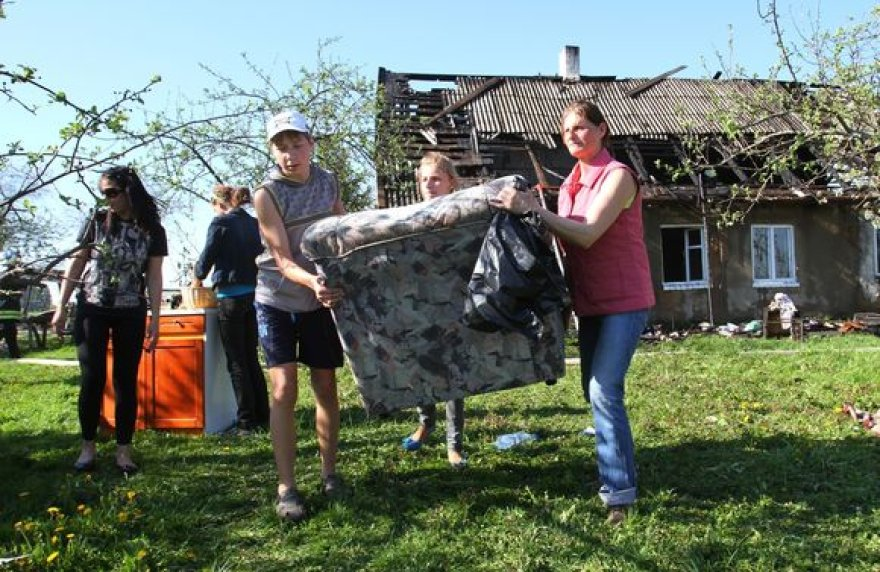 Po gaisro žmonės nešė iš namo daiktus.