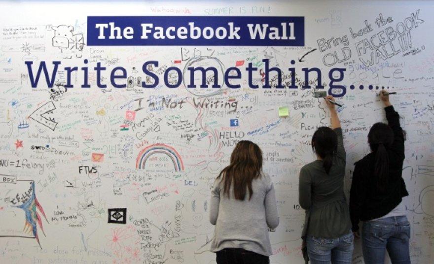 """""""Facebook"""" darbuotojai rašo ant specialiai tam skirtos sienos, įrengtos kompanijos būstinėje."""