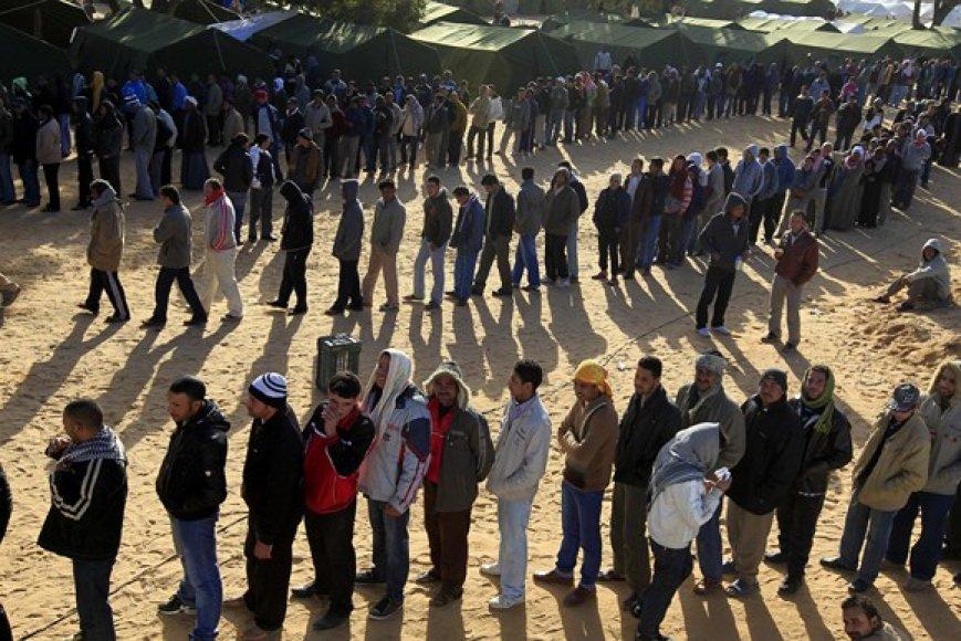 Išalkę ir pavargę žmonės pabėgėlių stovykloje laukia eilėje prie maisto.