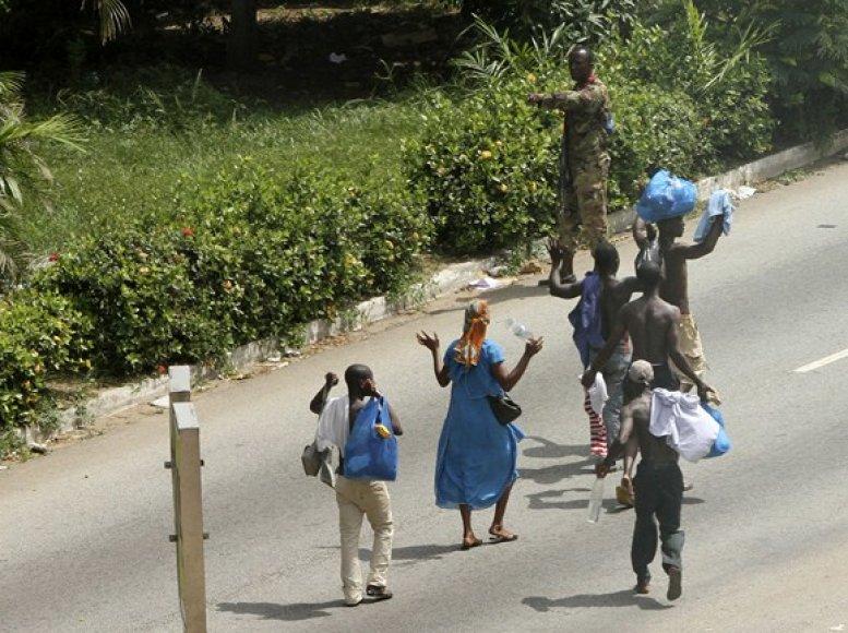 Vietos gyventojai iškėlę rankas eina pro Laurento Gbagbo kareivius