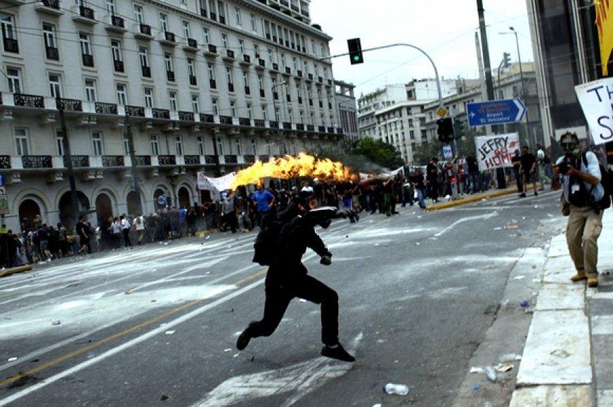 Protestuotojas meta Molotovo kokteilį.