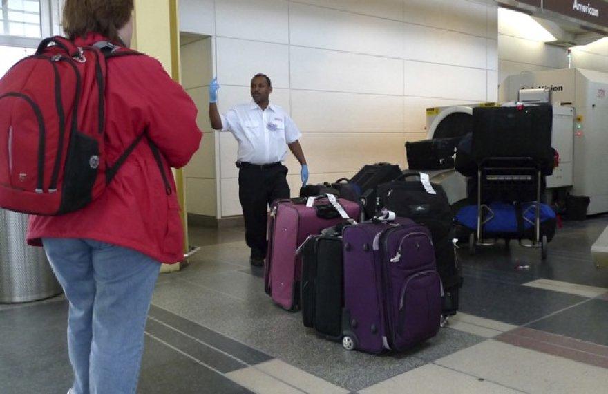 Oro uosto darbuotojas ruošia bagažą tikrinimui ir pakrovimui į lėktuvą