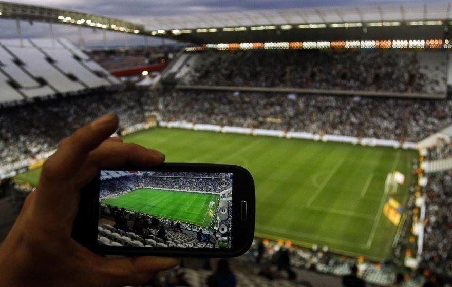 Išmaniuoju telefonu fotografuojamas futbolo stadionas
