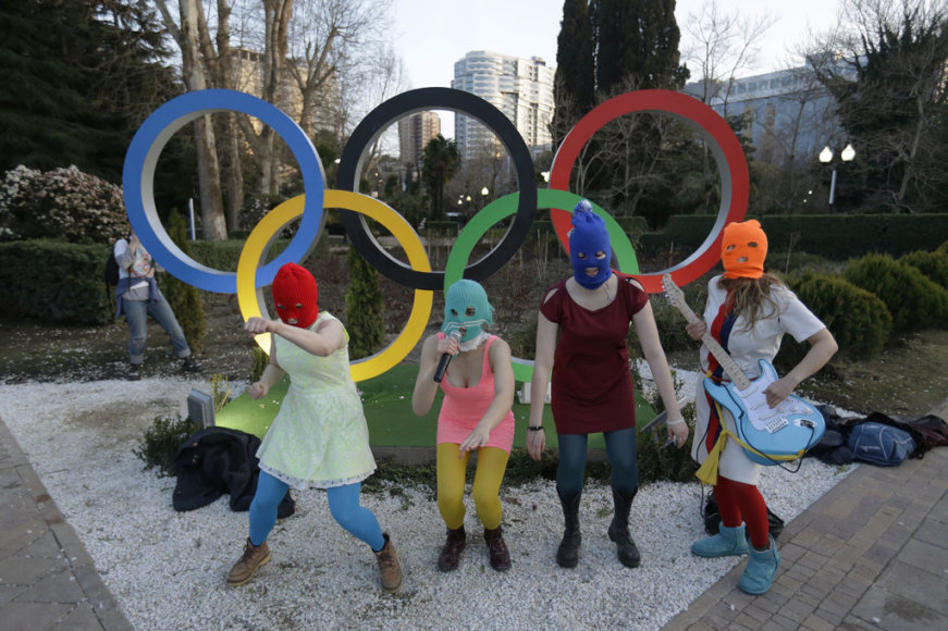 Members of the punk group Pussy Riot, including Nadezhda Tolokonnikova in the aqua balaclava, center, and Maria Alekhina in the red balaclava, left, perform next to the Olympic rings in Sochi, Russia, on Wednesday, Feb. 19, 2014. Cossack militia attacked the punk group with horsewhips earlier in the