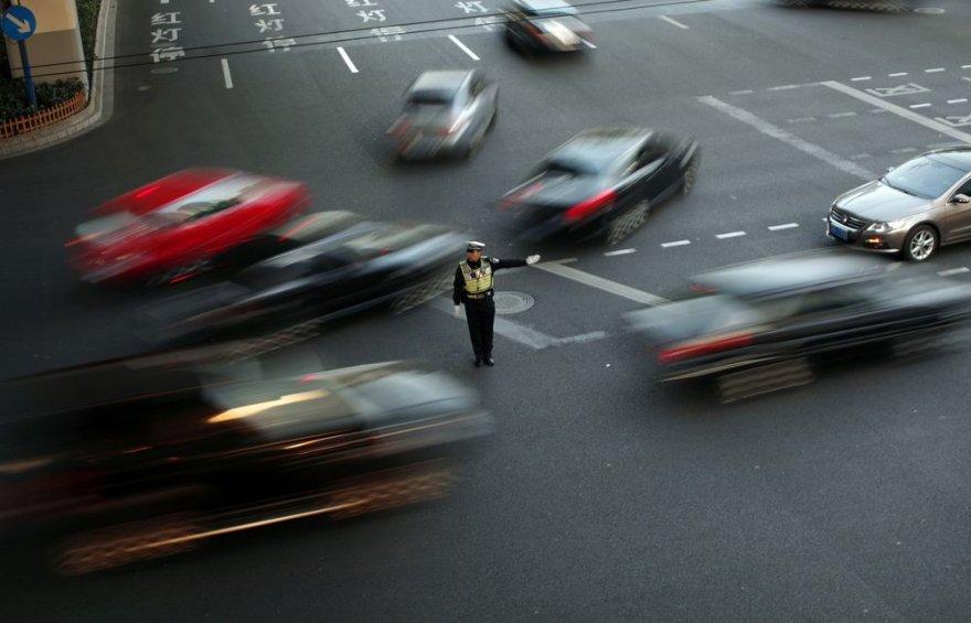 Policininkas reguliuoja eismą intensyvaus eismo gatvėje Šanchajuje