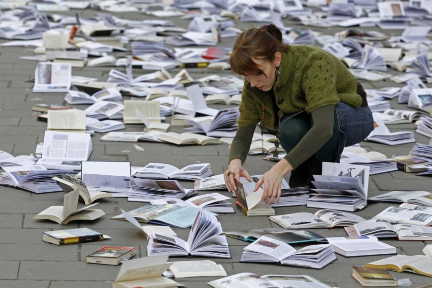 Moteris išdėlioja knygas renginiui skirtam pasaulinei knygos ir autorinių teisių dienai Bukarešte
