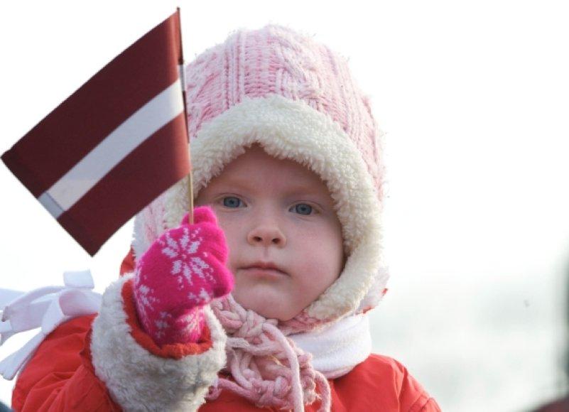 Latvijos vėliava vaiko rankose