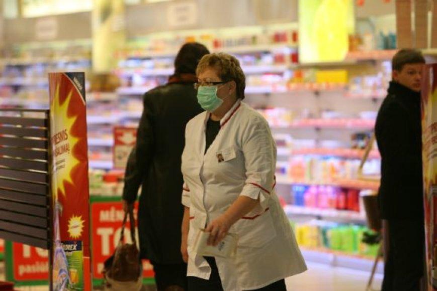 Vaistinės darbuotoja nuo siautėjančio gripo saugosi dėvėdama kaukę.