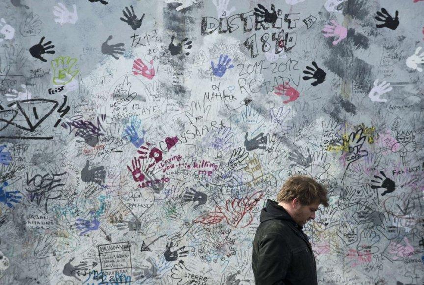 Vyras šalia Berlyno sienos