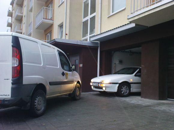 Užstatytas garažas. lengvasis automobilis bando išvažiuoti...