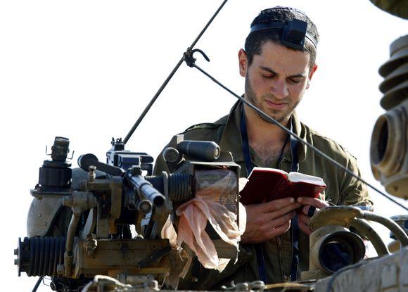 Izraelio karys išlipęs iš tanko skaito maldaknygę.