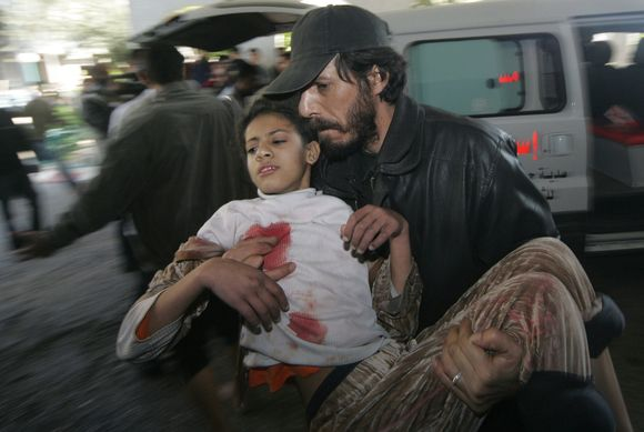 Vyras neša sužeistą mergaitę Gazos ruože.
