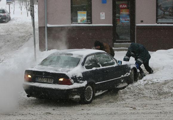 Kauniečiai stumia mašiną.