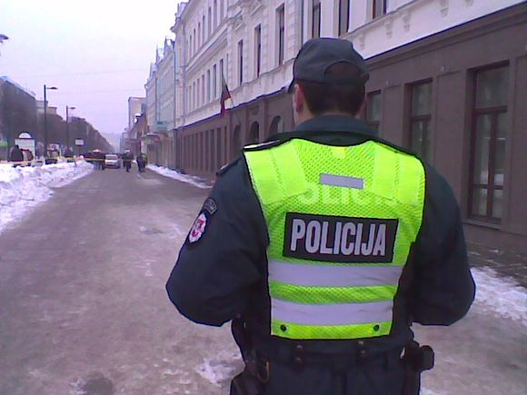 Policininkas rūpinasi praeivių saugumu.