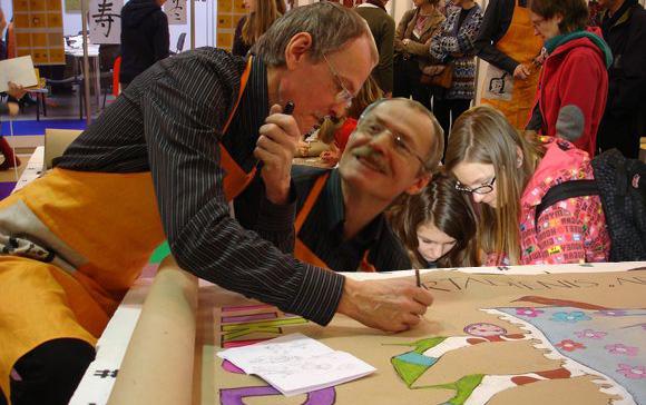 K. Kasparavičius su vaikais piešia žirafą