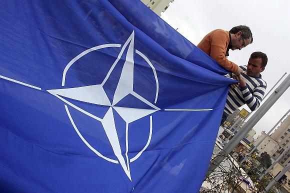 Darbininkai Tiranoje, Albanijos sostinėje, rengiasi iškelti NATO vėliavą.