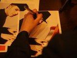 Alvydo Opulskio/15min.lt nuotr./Sasha Son pasirašėja naujuoju rašikliu.