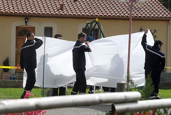 Žandarai nuo pašalinių akių uždengia iš savo namų Kabanake išgabenamą vienos iš aukų lavoną.
