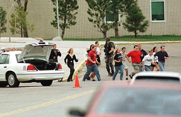 1999-ųjų balandžio 20-ąją vaikai bėga iš mokyklos, kurioje du paaugliai vykdė žudynes.