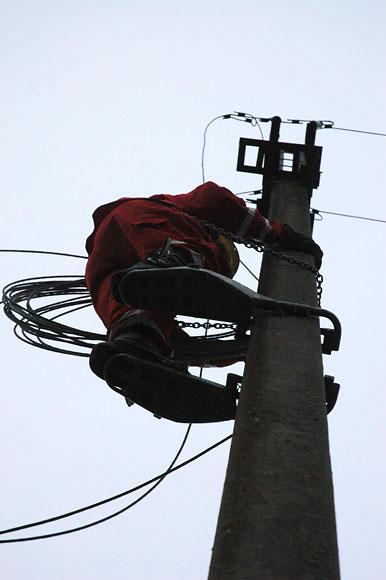Į stulpą įlipęs elektrikas