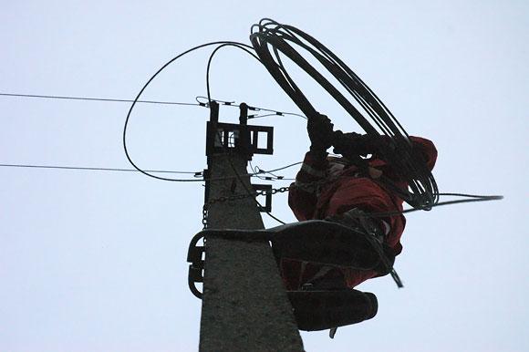 Elektrikas tvarko per avariją nutrauktus laidus