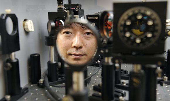 Jamesas Chonas iš Svinburno technologijos universiteto Australijos Melburno mieste atsispindi optinio įrašymo aparato filtre.