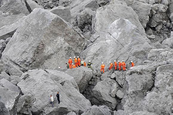 Kinijos gelbėtojai milžiniškos nuošliaužos vietoje ieško išgyvenusių tautiečių.