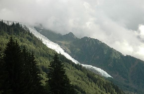 Monblanas slepiasi už debesų. Matyti tik nuo kalno slenkantis ledynas (centre)