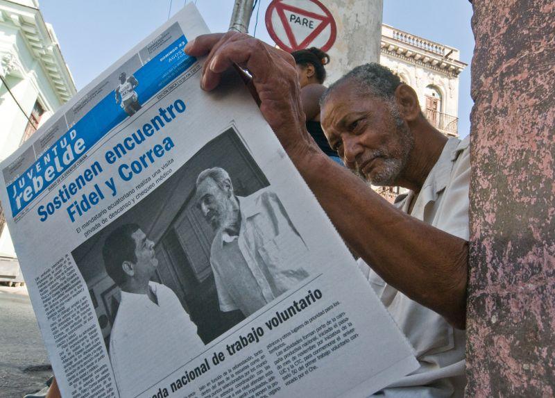 Žmogus Havanoje skaito laikraštį su F.Castro nuotrauka