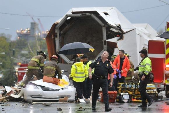 AP nuotr./Gelbėtojams teko vaduoti automobilio, ant kurio užvirto medis, viduje įstrigusį vyrą  57 metų Michaelą Williamsą.