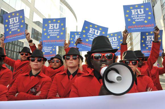 """Aktyvistai pasitiko ES vadovus su plakatais, raginančiais """"sumokėti klimato skolą""""."""
