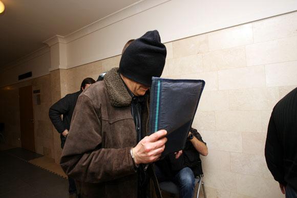 Į teismo rūmus vedamas įtariamasis kaip įmanydamas bandė slėpti savo veidą.